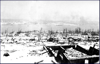A view across the devastation of Halifax, looking toward the Dartmouth side of the harbour. IMO can be seen aground on the far side of the harbour after the explosion - Halifax 6th December 1917.