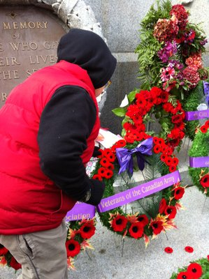 Aidan laying a poppy on a wreath